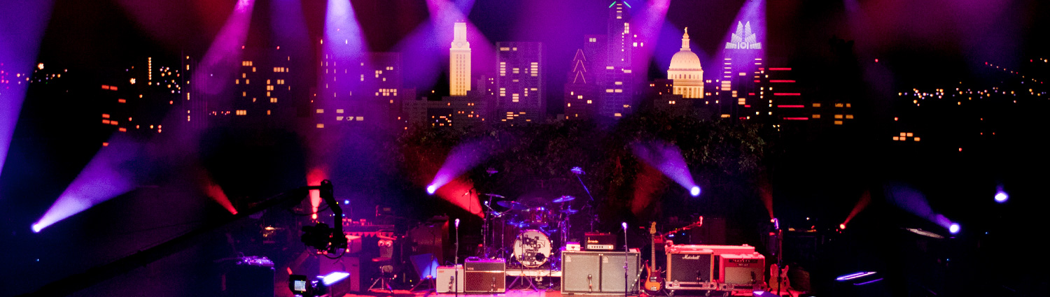The Austin City Limits stage, coverd with insturments like guitars, a drumset, and keyboards, lit up with stage lights, and the Austin City Limits backdrop.